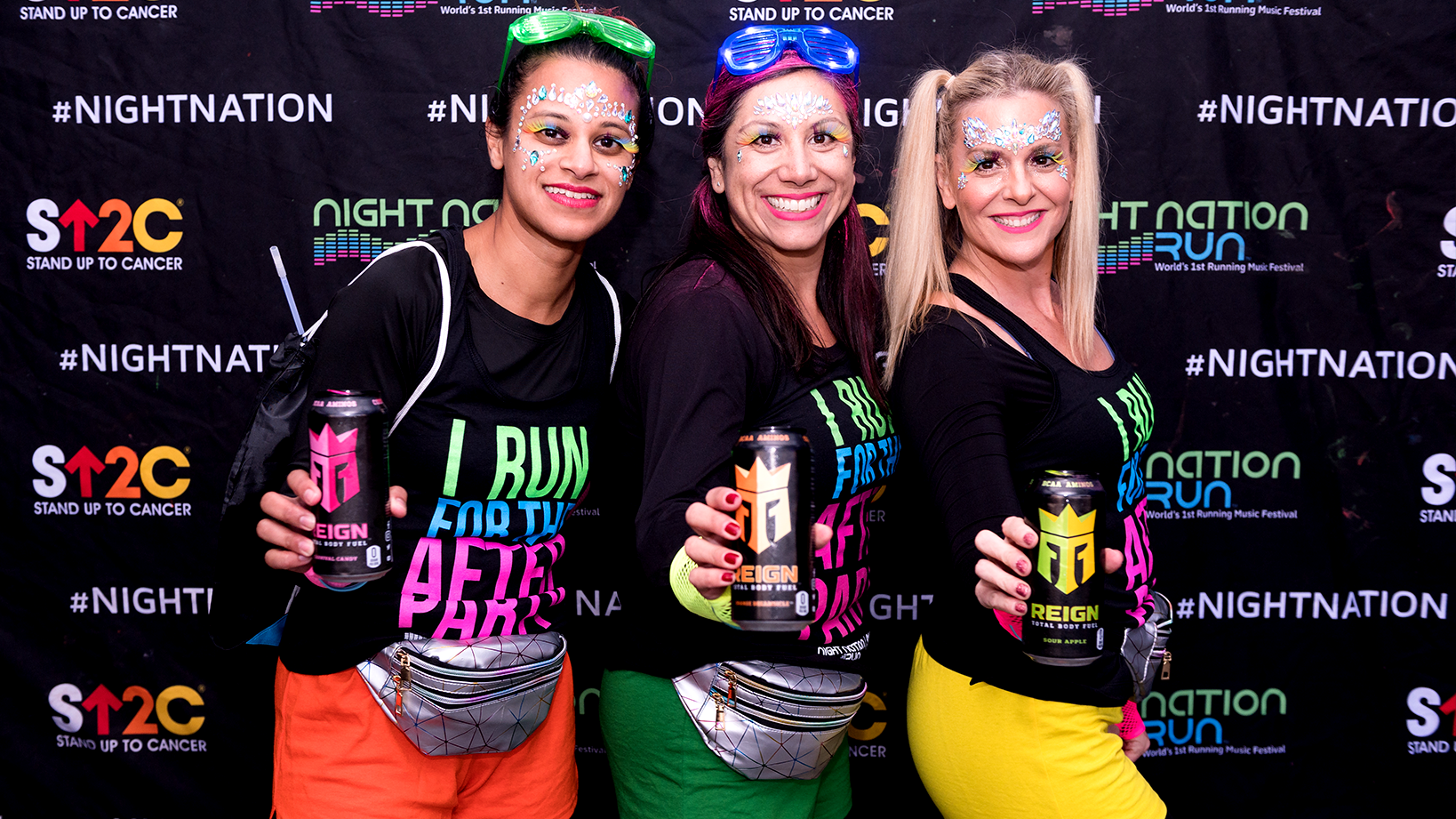 Women posing for a photo with Reign cans