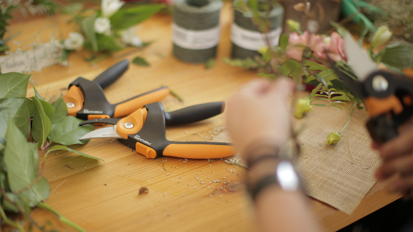 Person using Fiskars tools to cut flowers